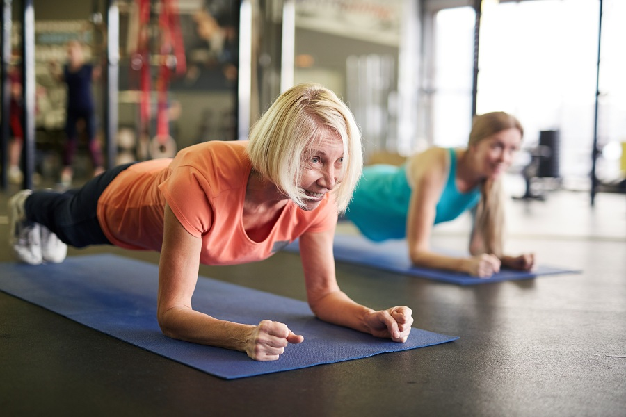 women in plank position at the gym